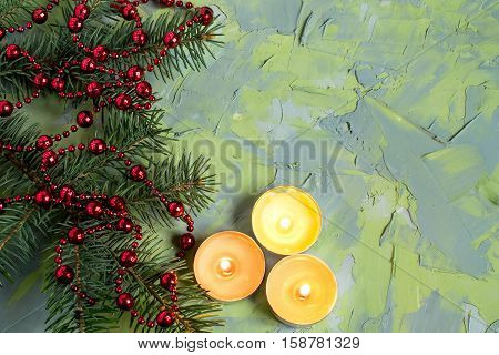 Festive Christmas background with candles and with branches of spruce decorated with red beads on the textured surface of the blue and green putty. Empty space for text