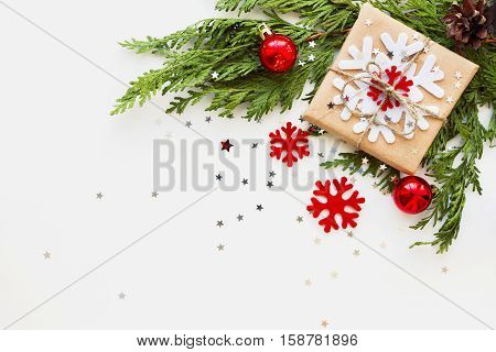 Christmas and New Year background with thuja branch decorations and present wrapped in craft paper with snowflakes. Flat lay top view. Place for text.