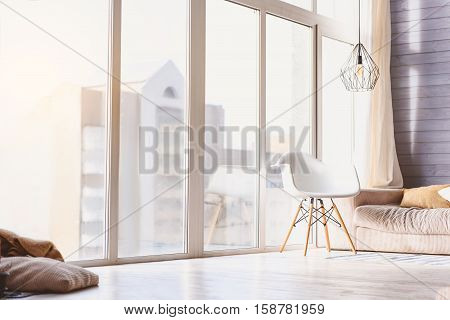 Relaxing view from window in cozy living room with modern interior. Chair near sofa on floor