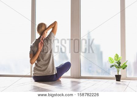 Young woman is undergoing morning exercise. She is sitting and stretching arms behind back. Lady is looking at window and enjoying urban view