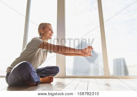 Happy young woman is doing yoga with enjoyment at home. She is sitting near window and stretching arms forward. Lady is laughing