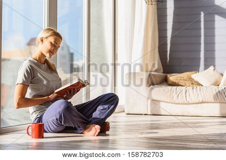 Peace and pleasure. Relaxed young woman is reading book at home. She is sitting near window and cup of tea. Lady is smiling