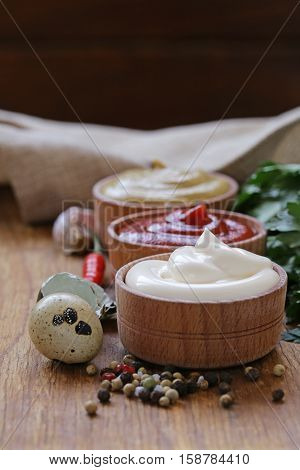 Ketchup, mayonnaise and mustard - three kinds of sauce in a wooden bowl