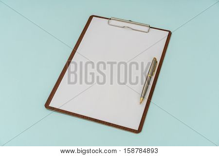 Clip board , pen and paper on blue background