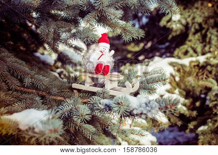 Christmas background with a snowman sitting on a sled