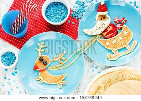 Christmas fun food for kids funny breakfast idea - creative pancakes with cream fruit and berry shaped Santa Claus riding reindeer sleigh on Christmas