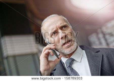 Grizzled man making a troubled phone call