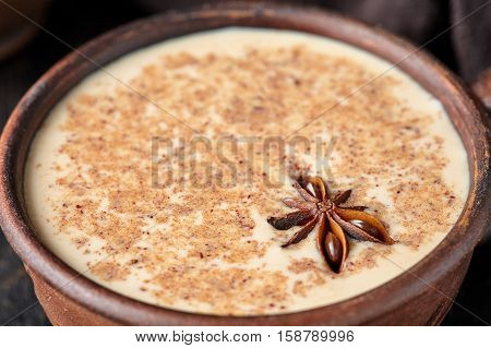 Masala tea chai latte traditional warm Indian sweet milk spiced drink, ginger, fresh spices blend organic infusion healthy wellness beverage in rustic clay cup on dark table background