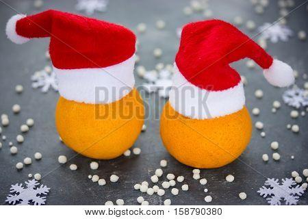 Tangerine in Santa hat Christmas Xmas New Year concept fresh ripe and sweet mandarin orange clementine tangerine symbol winter holidays