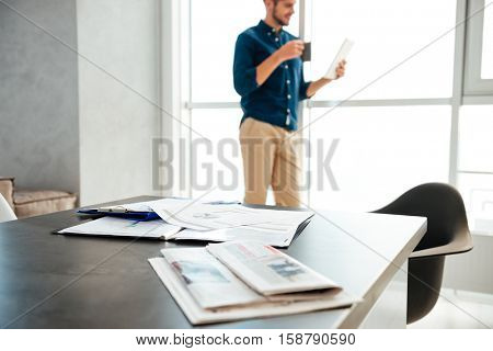 Picture of man's table with documents and newspapers. Young man standing near big window and drinking coffee while reading newspaper at the background. Focus on documents and newspapers.