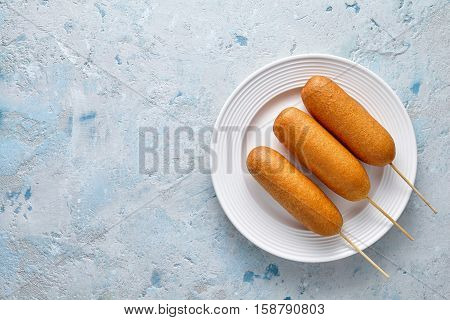 Corn dog traditional American corndog street junk food deep fried hotdog meat sausage snack treat coated in a thick layer of cornmeal batter on stick unhealthy eating on rustic table background.