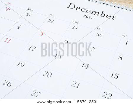 December on white calendar page desk calendar on wood background (Selective focus)