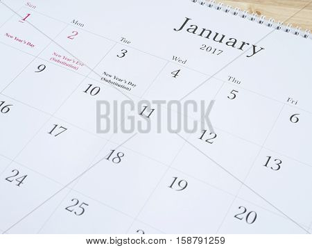 January on white calendar page desk calendar on wood background (Selective focus)