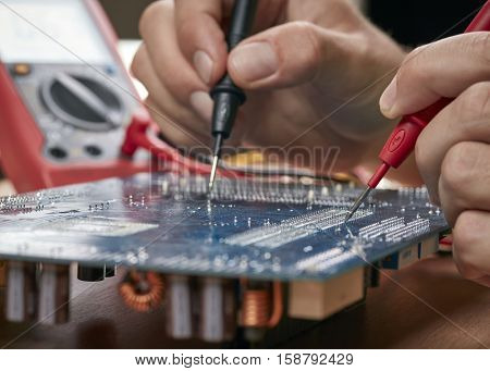 Technician checking motherboard with tester. Technological background. Shallow DOF