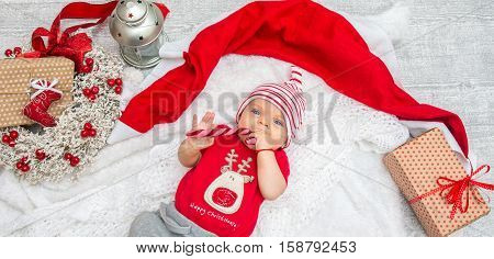 Christmas Baby Girl Six Months On The Eve Of Christmas With Candy And Gift.