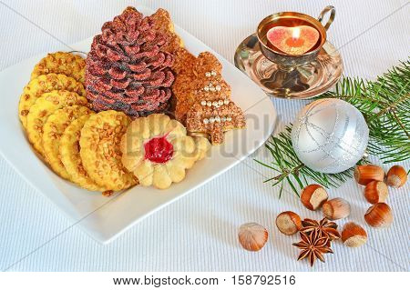 Shortbread biscuits candle Christmas decorations and fir branches on the table