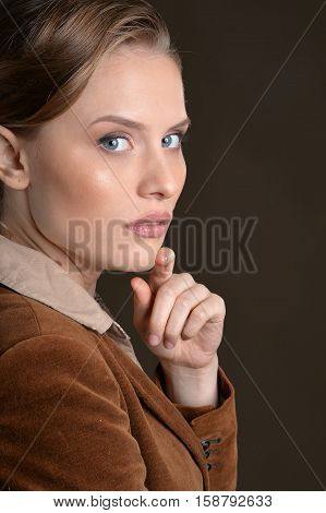 Portrait of young serious woman looking at camera against grey background