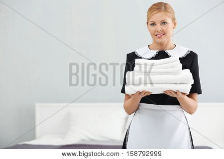 Chambermaid holding pile of clean towels in the room