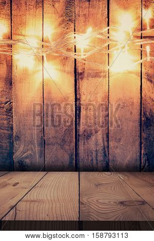 Christmas Light On Wooden Background And Wooden Table. Christmas Table Background With Space For Pro