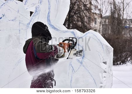 Worker using a chainsaw carving an ice sculpture