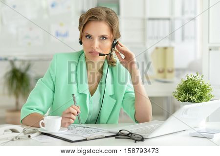 Portrait of young businesswoman in headset working in the office and looking at the camera