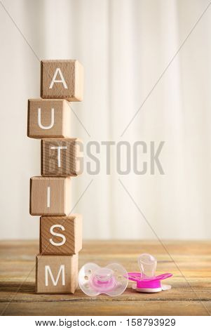 Wooden cubes with word autism and pacifiers on light background