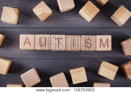 Wooden cubes with word AUTISM on wooden background