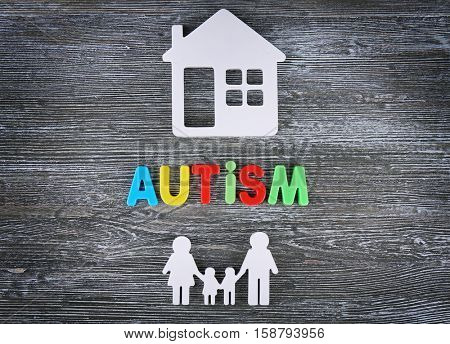 Word Autism with figures on wooden background