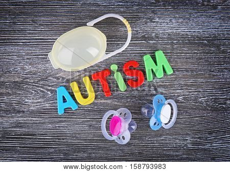 Word Autism with pacifiers on wooden background