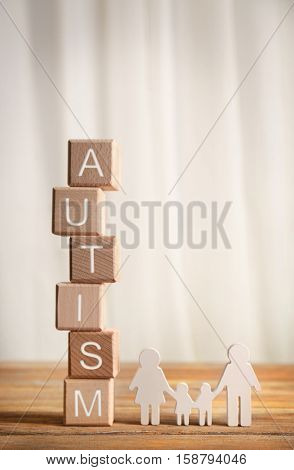 Wooden cubes with word autism and family shape toy on light background