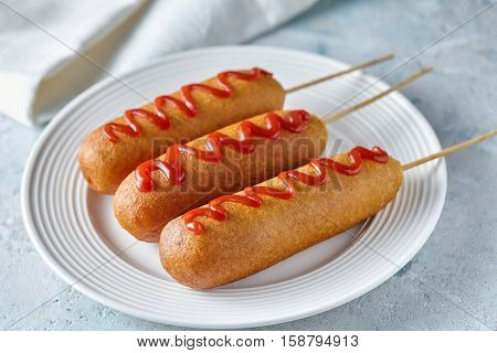 Corn dog traditional American corndog street junk food deep fried hotdog meat sausage with ketchup snack treat coated in a thick layer of cornmeal batter on stick unhealthy eating on rustic table.