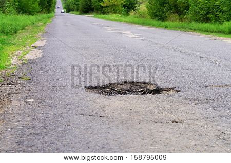 dangerous pothole in the asphalt highway summer