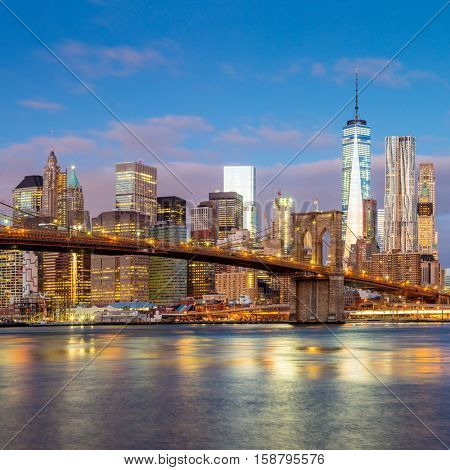Sunrise view of  Brooklyn Bridge and Lower Manhattan skyline in New York City with city illumination, USA