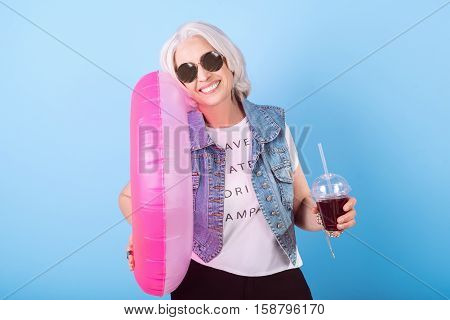 Summer is coming. Glad senior beautiful woman smiling and holding cocktail and ring lifebuoy while standing against isolated blue background.