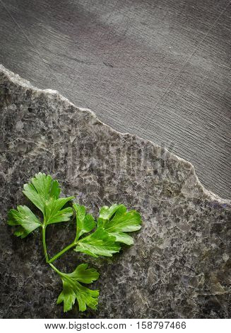 parsley leaves on a dark polished stone with an irregular fracture. Against the background of ebony Top view, space for text