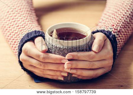 Hot mug of tea warming woman's hands in retro woollen jumper. Wooden table