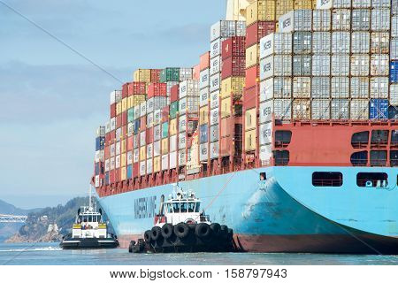 Oakland CA - October 11 2016: Cargo ships are unable to maneuver sideways. Multiple tugboats assist cargo ship GUNVOR MAERSK to maneuver sideways to the docks at the Port of Oakland