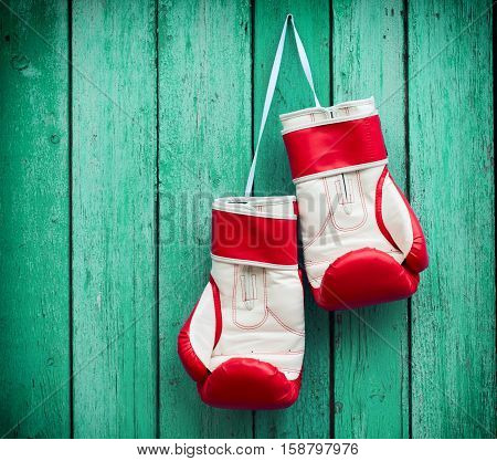 pair of red boxing gloves hanging on a nail on a background of green wood surface vintage toning