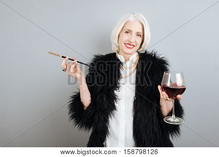 Pleasant relaxation. Beautiful pleasant senior woman smoking and drinking wine while standing against isolated gray background.