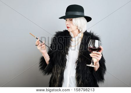 Aristocratic lifestyle. Presentable beautiful senior woman drinking wine and smoking cigarette while standing against isolated gray background.