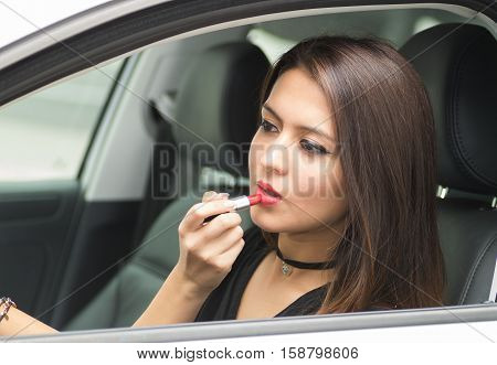 Closeup young woman sitting in car putting on makeup looking in mirror, as seen from outside drivers window, female driver concept.