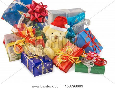 Teddy bear classic soft toy with Santa hat sitting in heap of gift boxes isolated over white. Time to make gifts. Horizontal.