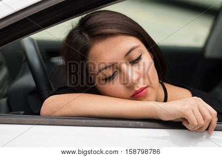 Closeup young woman sitting in car interacting tired and sleeping, as seen from outside drivers window, female driver concept.