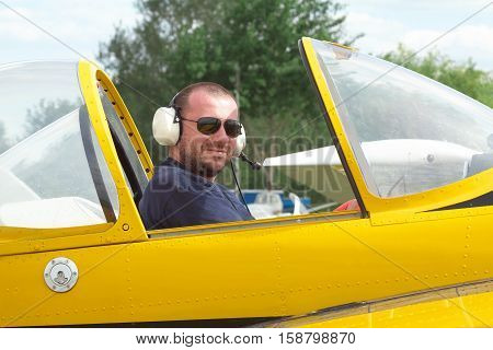 Smiling pilot sitting in the cockpit of a light aerobatic plane with the canopy open