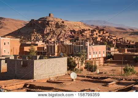View on a hill with an old medieval city Ait ben Haddou, built in red color. New building in the foreground Atlas mountains in the background. Blue morning sky.