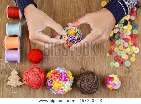 closeup of a young man making a handmade christmas ball with strings and buttons of different colors, and a pile of different haberdashery items on a rustic wooden surface