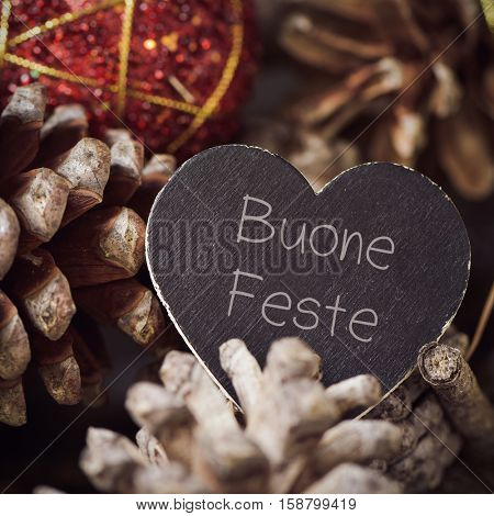 the text buone feste, happy holidays written in italian in a heart-shaped signboard and some pine cones and christmas balls