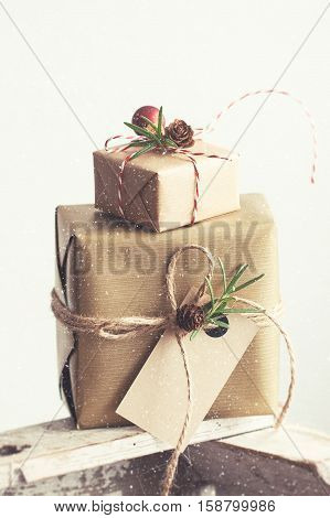 Christmas presents or gifts with elegant bow and christmas decorations wrapped in craft paper on bright background christmas concept