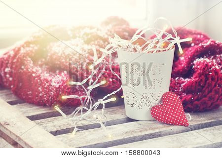 Cup with garland lights and red plush heart on a wooden background. Love valentine's day or good mood concept