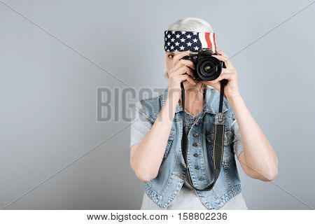 Favorite hobby. Pretty active senior woman concentrating and taking photo while standing against isolated gray background